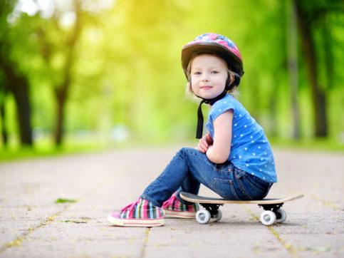 Cute little preteen girl wearing helmet sitting on a skateboard in beautiful summer park
