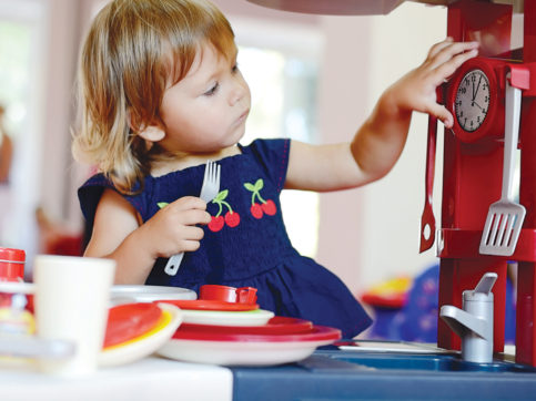 girl playing with kitchen set