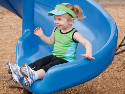 little girl sliding down blue slide