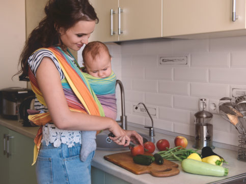 young mom with baby preparing food in the kitchen