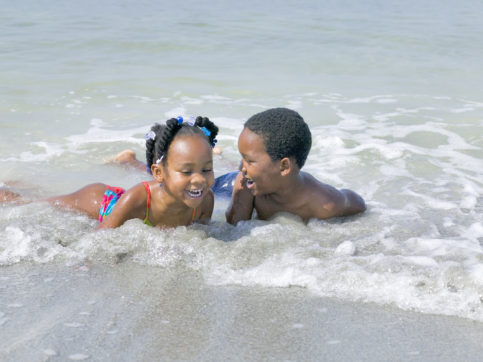 Young brother and sister enjoy a day playing at the beach