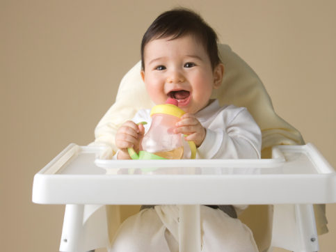 baby in highchair drinking out of a sippy cup