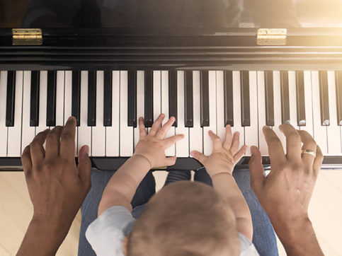 Baby learning to play piano with father
