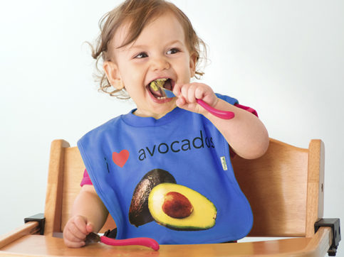 baby girl eating an avocado with toddler utensils