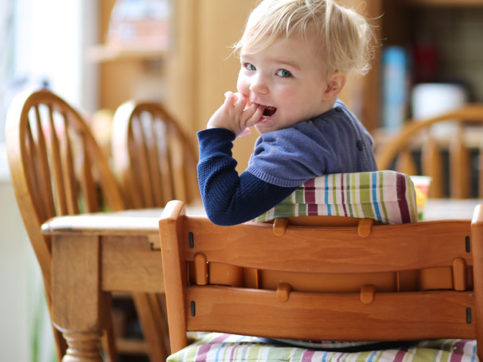 baby in highchair at table in the kitchen