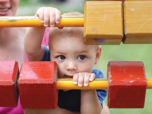 little boy looking through a playground